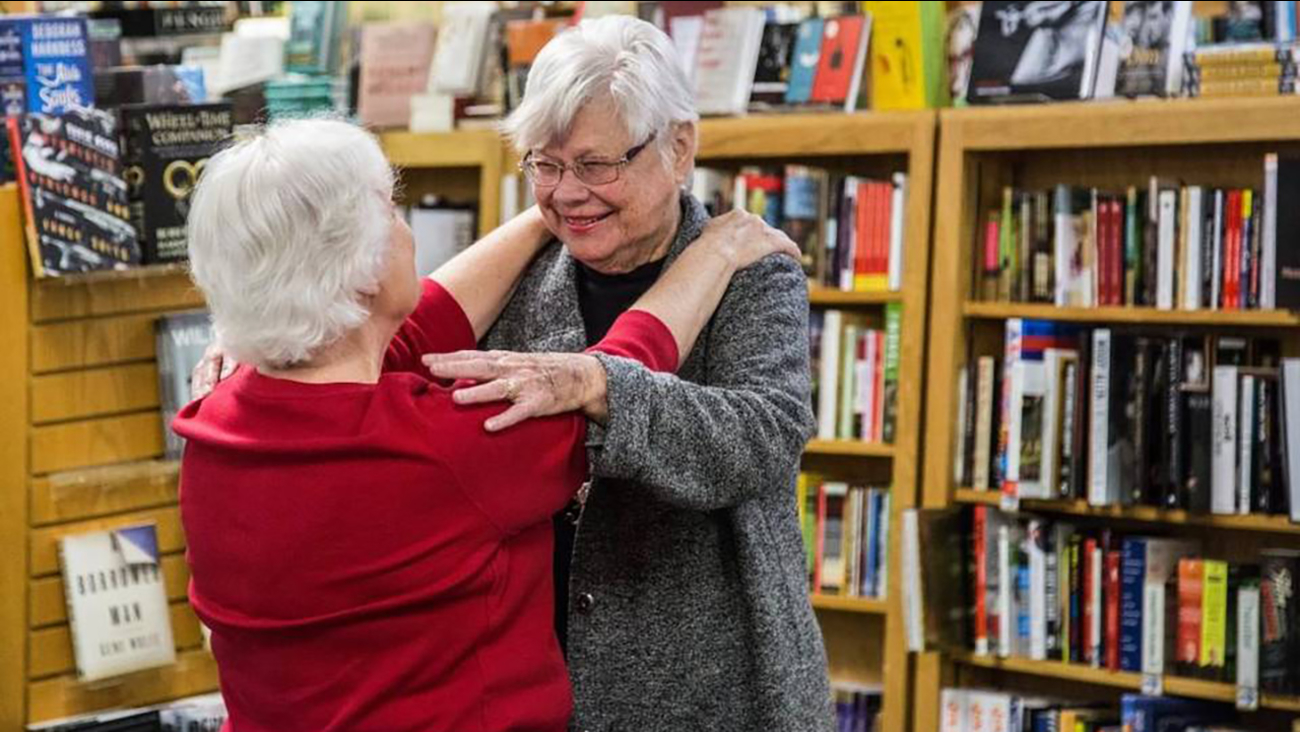 Raleigh writer's champion and Quail Ridge Books founder Nancy Olson hugs seasonal gift wrapper, Brenda Holloman, left, in December 2015 at the bookstore in Raleigh.
