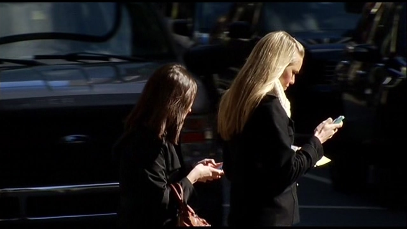 Two women text and walk down the street in this undated photo.