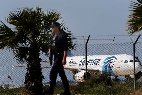"""<div class=""""meta image-caption""""><div class=""""origin-logo origin-image none""""><span>none</span></div><span class=""""caption-text"""">A police officer patrols outside the airport as a hijacked aircraft of EgyptAir is seen after landing at Larnaca Airport in Cyprus Tuesday, March 29, 2016. (Petros Karadjias/AP Photo)</span></div>"""
