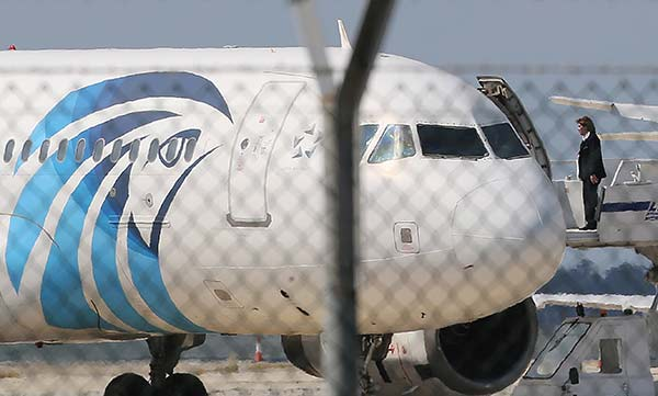 """<div class=""""meta image-caption""""><div class=""""origin-logo origin-image none""""><span>none</span></div><span class=""""caption-text"""">A crew member of the hijacked aircraft of EgyptAir is seen on the passenger steps after landing at Larnaca airport Tuesday, March 29, 2016. (Petros Karadjias/AP Photo)</span></div>"""