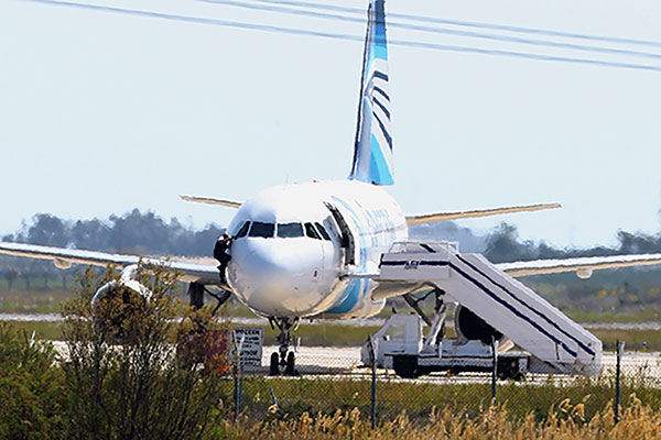 """<div class=""""meta image-caption""""><div class=""""origin-logo origin-image none""""><span>none</span></div><span class=""""caption-text"""">A man leaves the hijacked aircraft of Egyptair from the pilot's window after landing at Larnaca airport Tuesday, March 29, 2016. (Petros Karadjias/AP Photo)</span></div>"""
