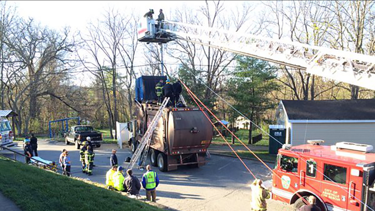 Crews work to rescue two men stuck in a trash truck