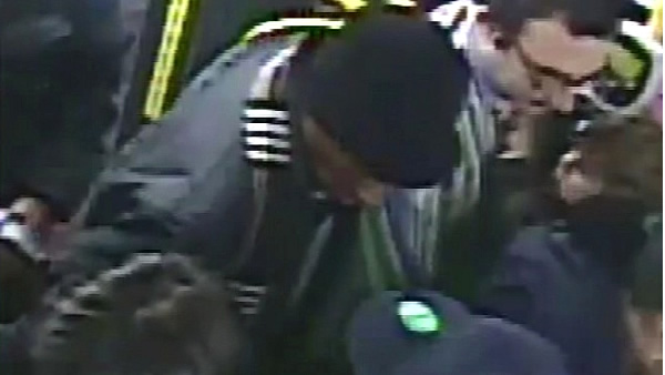 Surveillance video shows a man in a black hat accused of pickpocketing a man holding a bay on Muni in San Francisco, Calif.