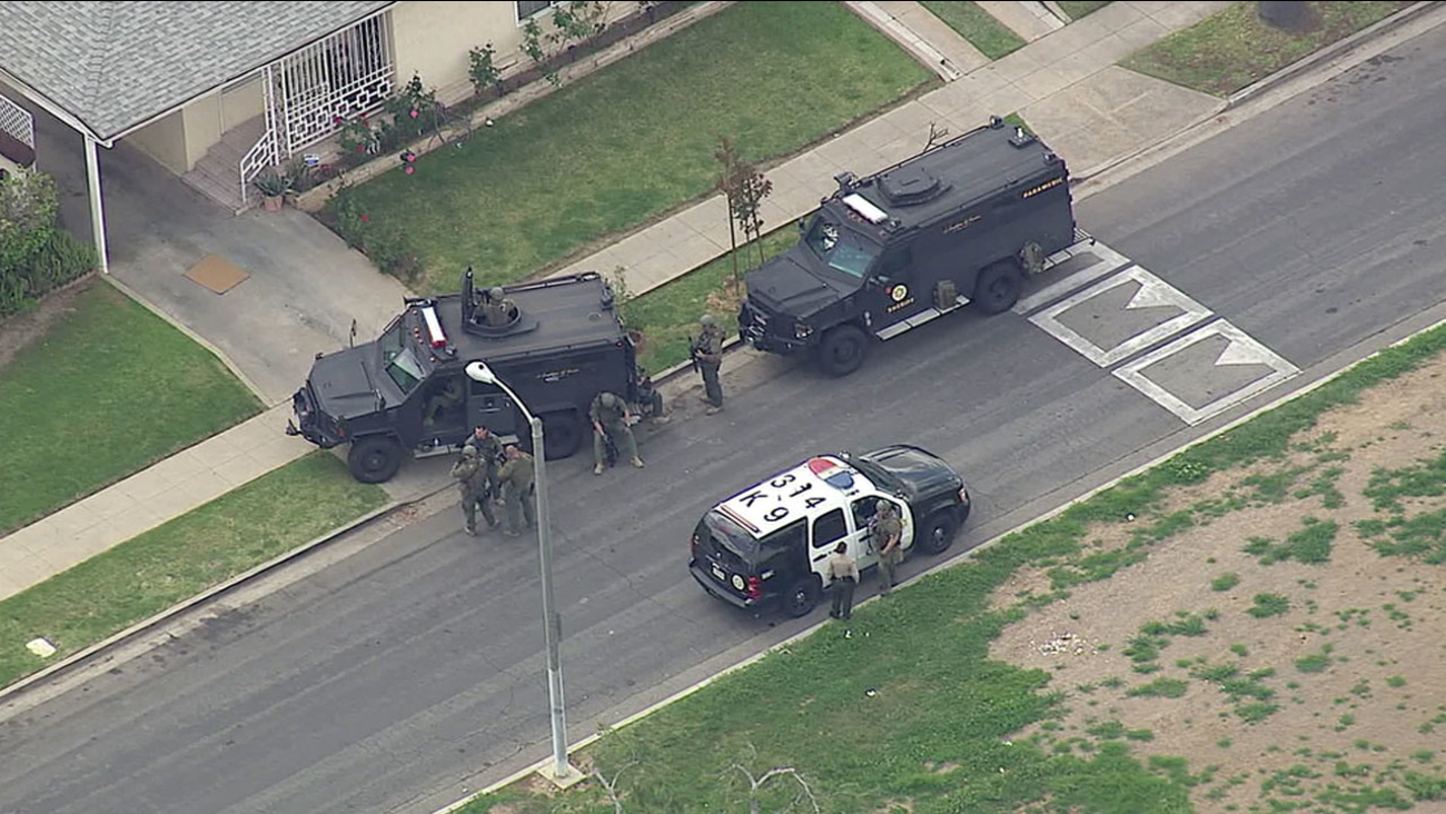 SWAT officers surround a home in East Los Angeles during a barricade situation on Wednesday, March 31, 2016.