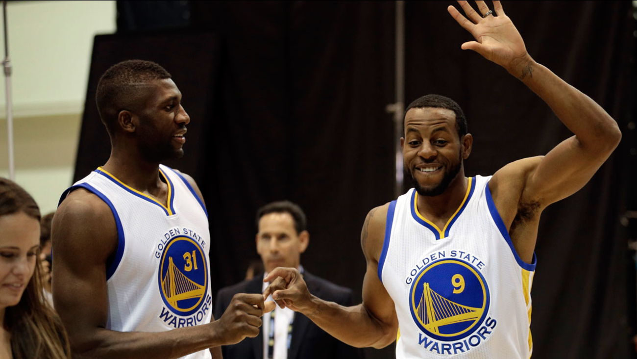 Golden State Warriors' Festus Ezeli, left, and Andre Iguodala (9) greet one another during an NBA basketball media day Monday, Sept. 28, 2015, in Oakland, Calif.