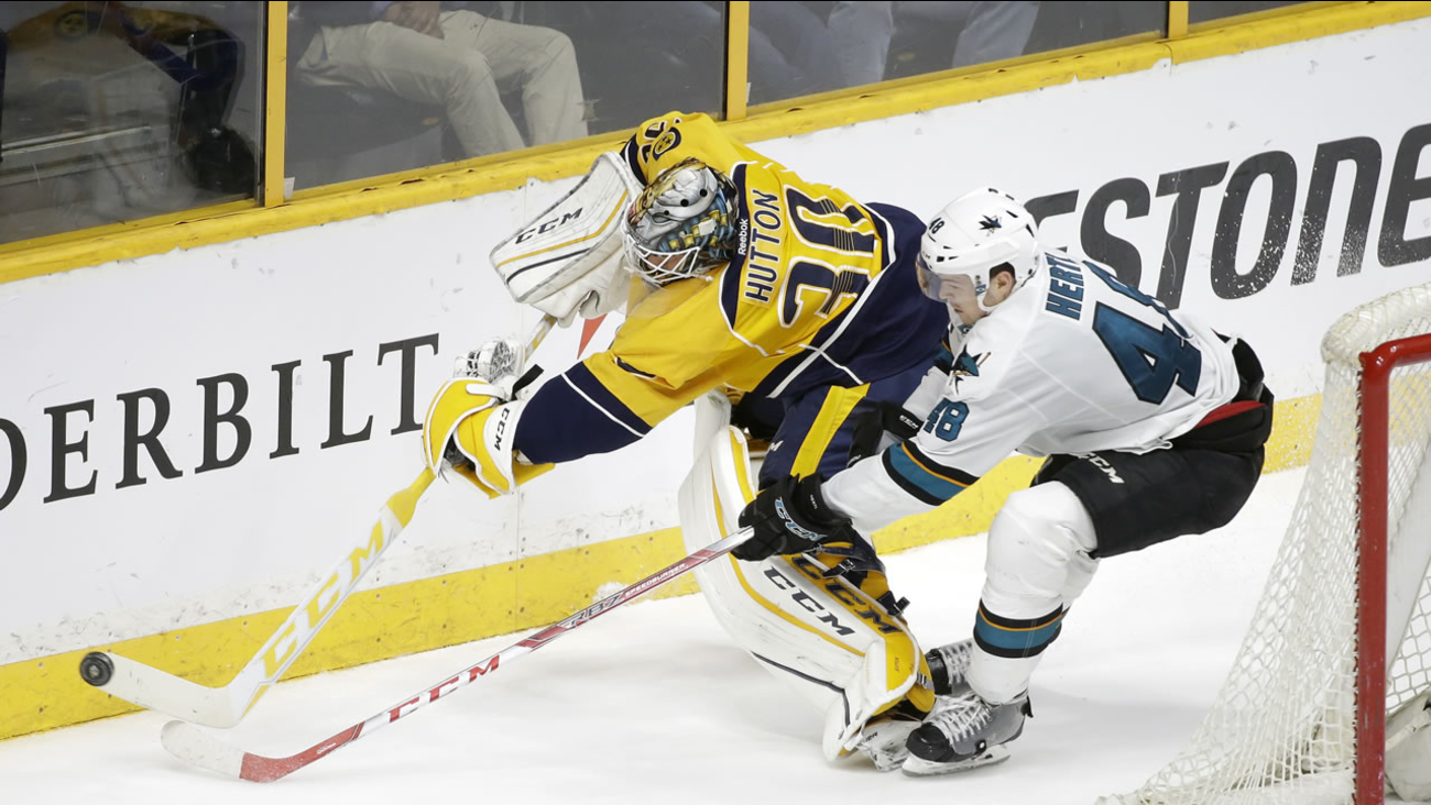 Nashville Predators goalie Carter Hutton (30) clears the puck ahead of San Jose Sharks center Tomas Hertl (48), during a  NHL hockey game April 2, 2016, in Nashville, Tenn.