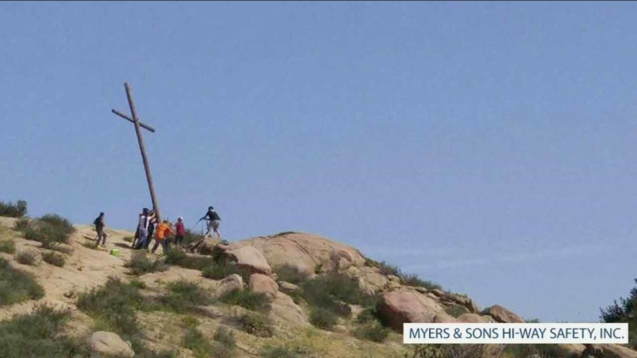 Riverside community members help fix a 20-foot cross that was chopped down by suspected vandals.