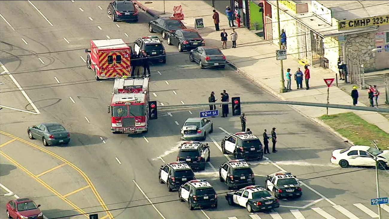 Law enforcement and fire officials are shown at the scene of a car crash and stabbing near Broadway and 92nd Street in Los Angeles on Wednesday, April 6, 2016.