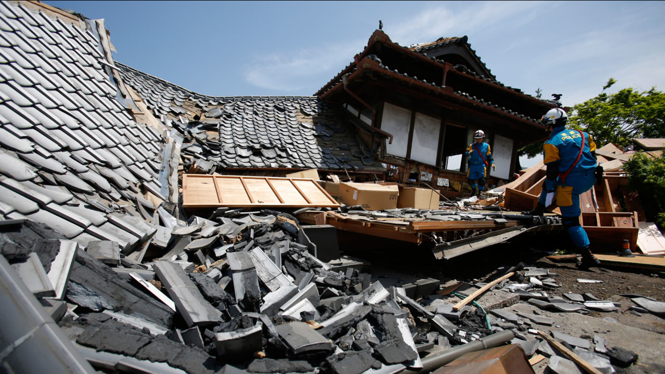 Police rescue team members search through damaged houses to check for trapped people in Mashiki, Kumamoto prefecture, southern Japan, Friday, April 15, 2016.