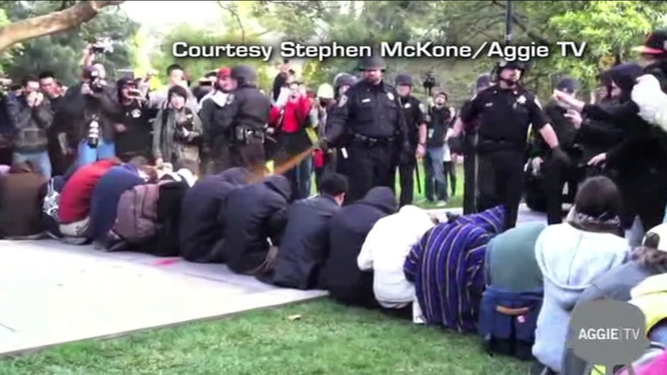 This image shows a UC Davis campus police officer pepper-spraying student protesters in 2011 in Davis, Calif.