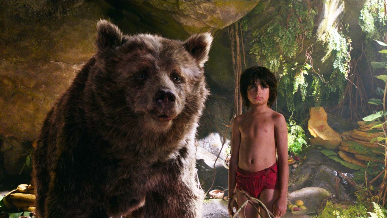 "In this image released by Disney, Mowgli, portrayed by Neel Sethi, right, and Baloo the bear, voiced by Bill Murray, appear in a scene from, ""The Jungle Book."""