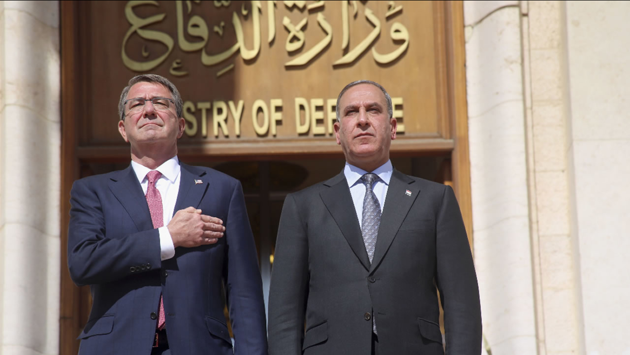 U.S. Defense Secretary Ash Carter his Iraqi counterpart Khaled al-Obeidi stand for their country's national anthems at the Ministry of Defense, Baghdad, Iraq, Mon., April 18, 2016.
