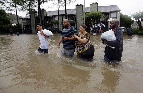 "<div class=""meta image-caption""><div class=""origin-logo origin-image ap""><span>AP</span></div><span class=""caption-text"">Darius Simon, second from left, helps his mother Carol, evacuate her flooded apartment complex along with his brother Dominique and son, Isaac Hernandez. (AP Photo/David J. Phillip)</span></div>"