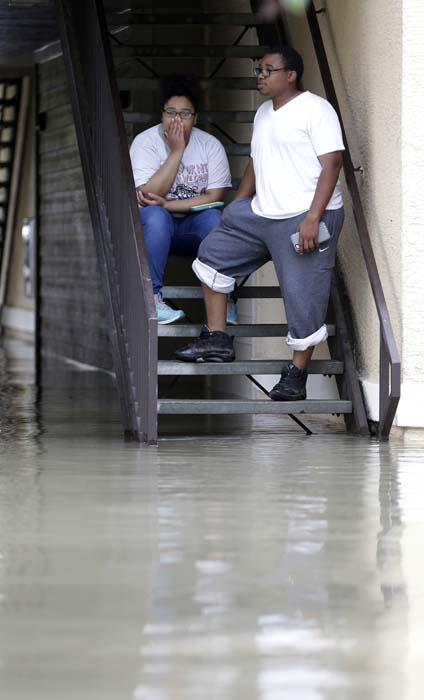 <div class='meta'><div class='origin-logo' data-origin='AP'></div><span class='caption-text' data-credit='AP Photo/David J. Phillip'>Deidra Andrews, left, waits with her husband Robert Darensburg to be evacuated from their flooded apartment complex</span></div>