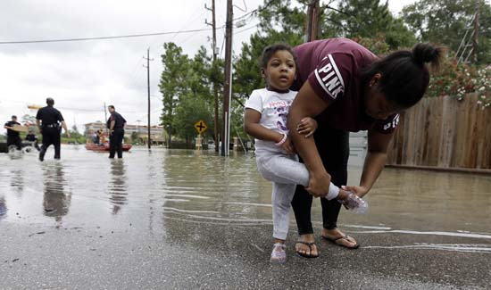 "<div class=""meta image-caption""><div class=""origin-logo origin-image ap""><span>AP</span></div><span class=""caption-text"">Brittany Parker puts a shoe back on her daughter Zoey after being rescued from their flooded apartment complex (AP Photo/David J. Phillip)</span></div>"