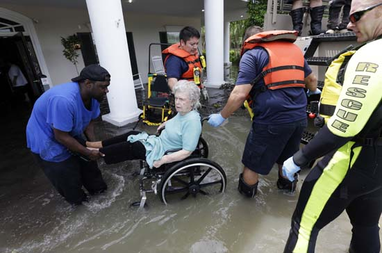 <div class='meta'><div class='origin-logo' data-origin='AP'></div><span class='caption-text' data-credit='AP Photo/David J. Phillip'>A resident of a retirement and assisted living complex is helped by rescue personnel as the facility is evacuated due to rising floodwaters</span></div>