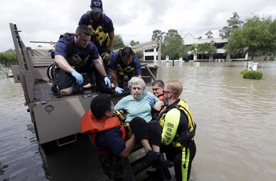 <div class='meta'><div class='origin-logo' data-origin='AP'></div><span class='caption-text' data-credit='AP Photo/David J. Phillip'>A resident of a retirement and assisted living complex is helped by rescue personnel</span></div>