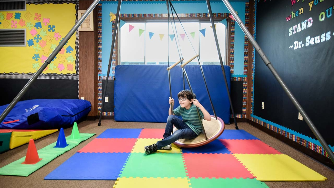 """John Dylan """"JD"""" Ronk tries out a new swing at Gabby's Room, a new sensory/motor skills center for the autistic program at Heaton Elementary School."""