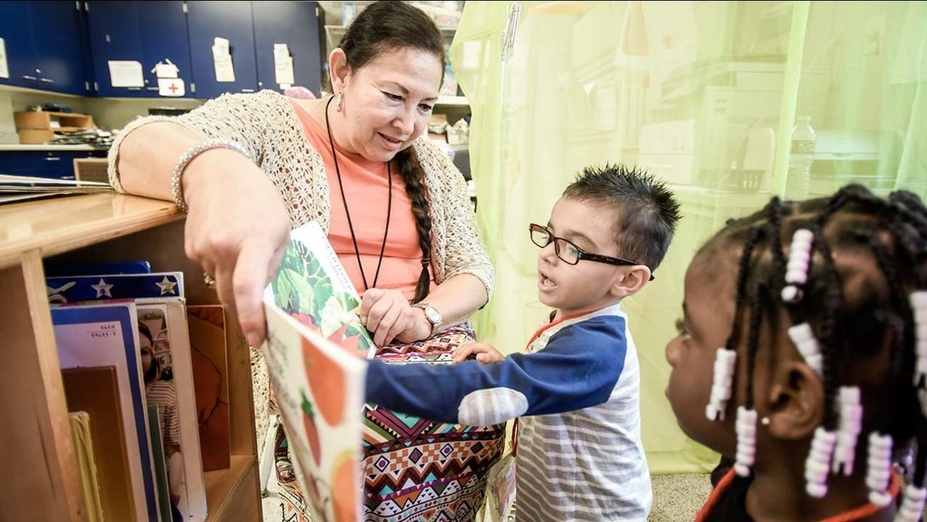 Wishon Elementary School preschool teacher Andrea Wall works with Sonny Molina while Jae'da Worthy waits her turn.