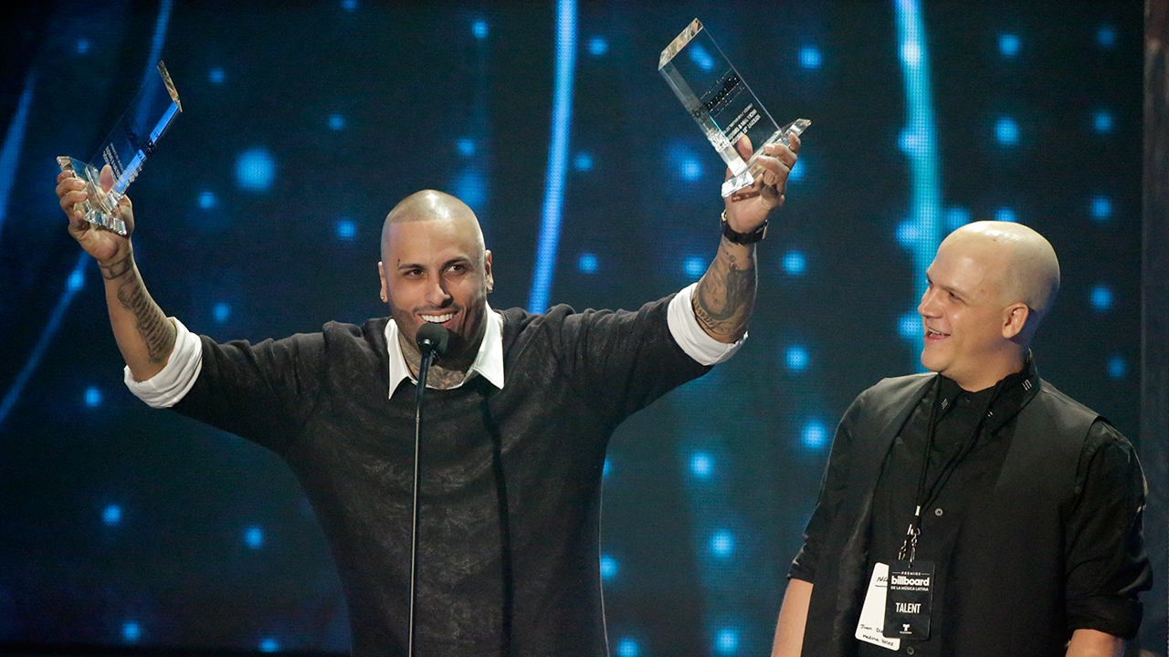 Singer Nicky Jam raises his Hot Latin Song of the Year during the Latin Billboard Awards, Thursday, April 28, 2016 in Coral Gables, Fla.