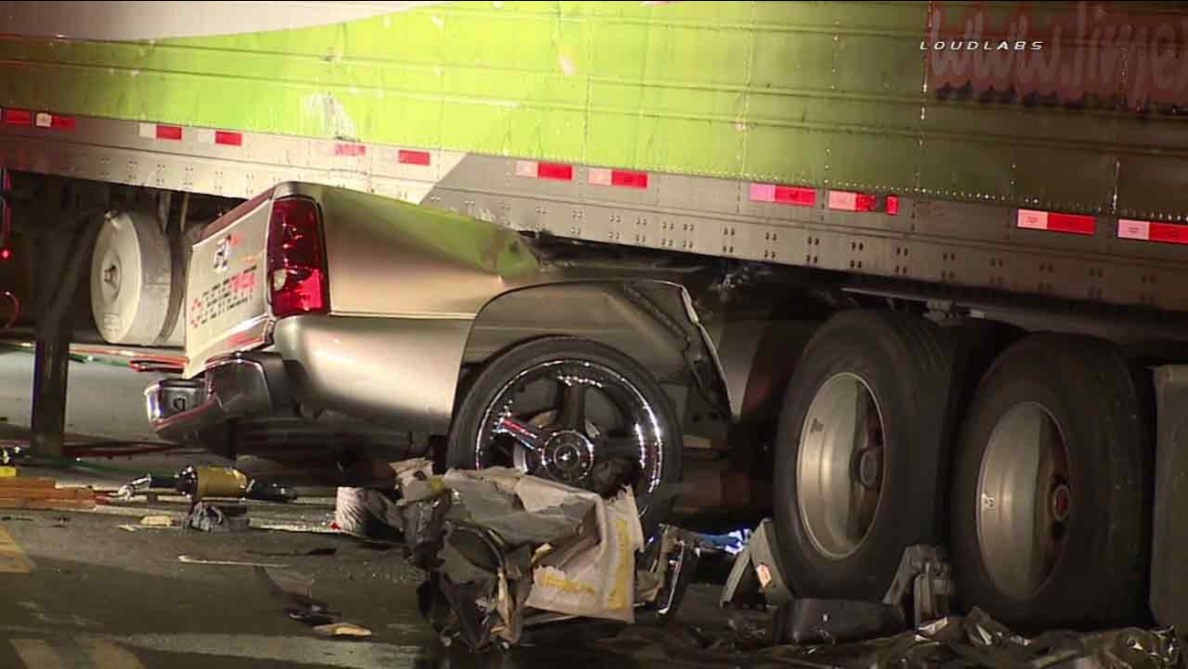 A pickup truck is seen trapped under a semi-truck after a deadly crash in Vernon, Calif., on Saturday, April 30, 2016.