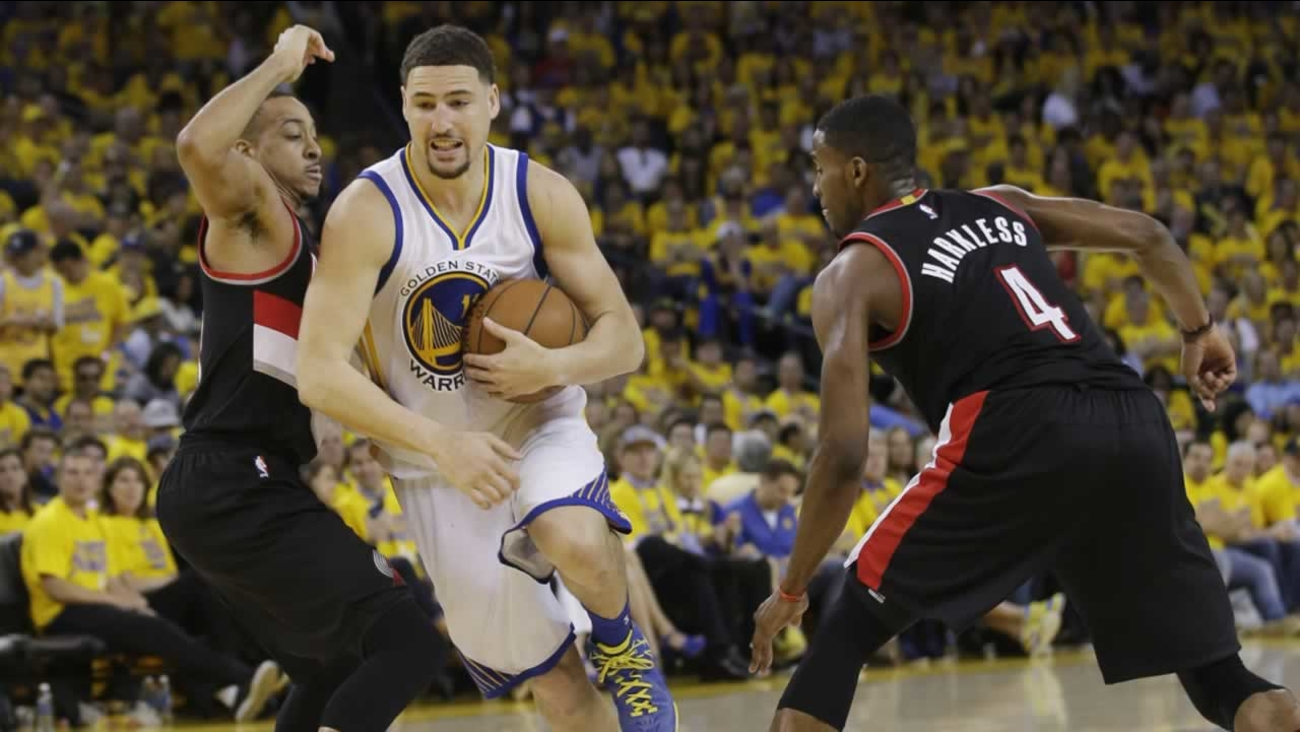 Warriors' Klay Thompson dribbles between Portland Trail Blazers' C.J. McCollum and Maurice Harkless on Sunday, May 1, 2016, in Oakland, Calif.