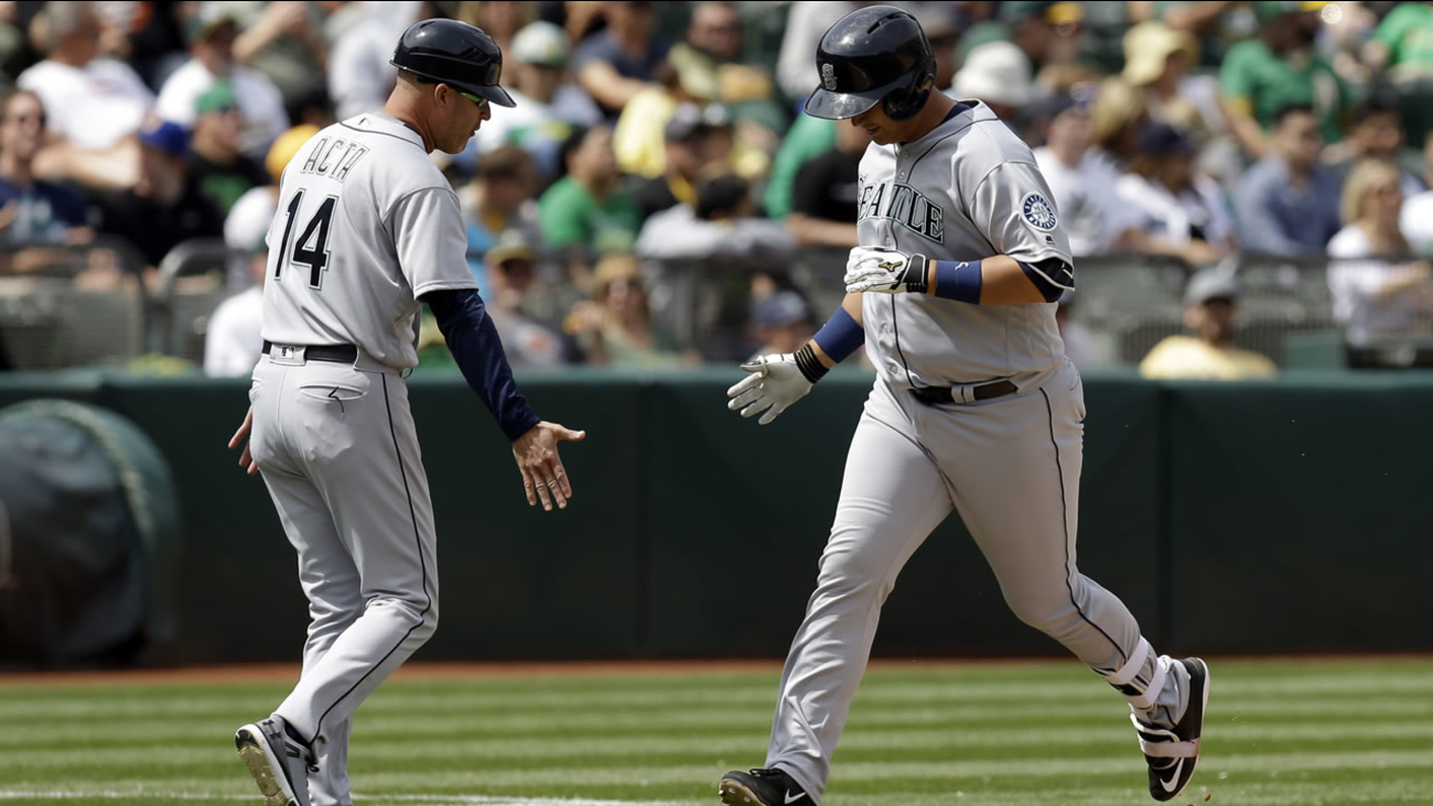 Mariners' Dae-Ho Lee  is congratulated by third base coach Manny Acta after hitting a two run home during a game in Oakland, Calif. on May 4, 2016. (AP Photo/Ben Margot)