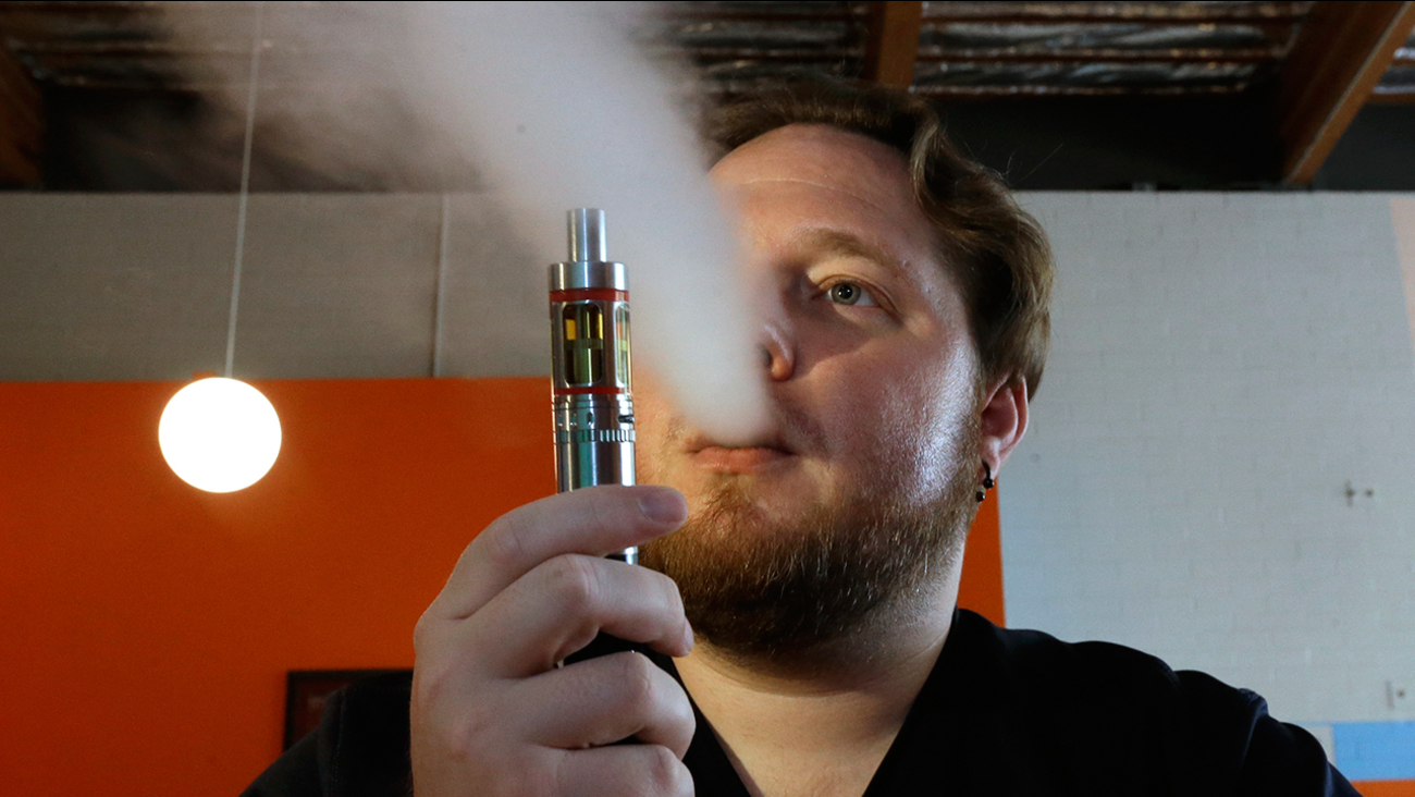 In this July 16, 2015 file photo, Bruce Schillin exhales vapor from an e-cigarette at the Vapor Spot