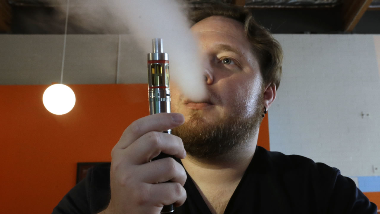 In this July 16, 2015 file photo, Bruce Schillin exhales vapor from an e-cigarette at the Vapor Spot, in Sacramento, Calif.