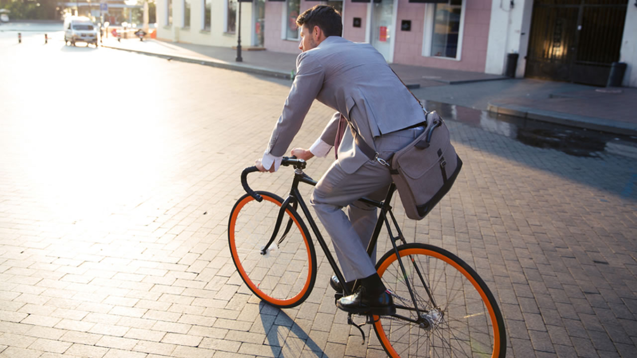 A businessman takes his bike to work.