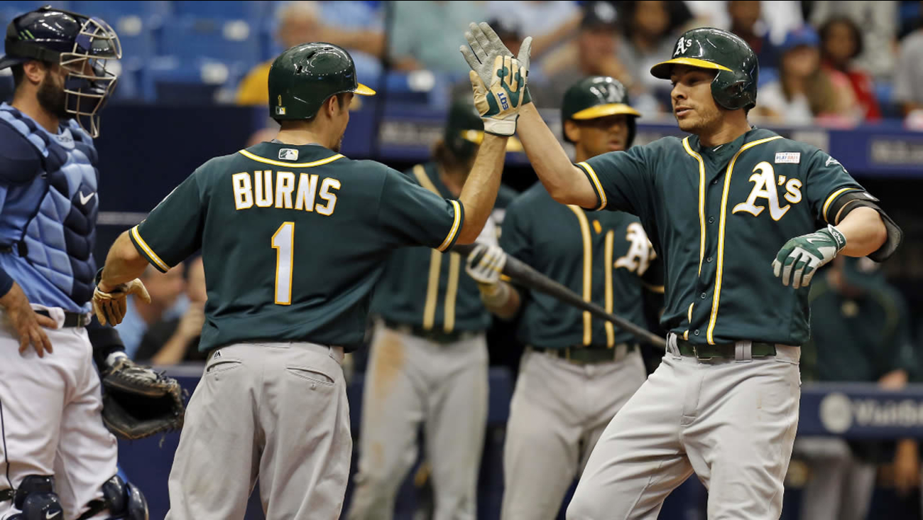 Oakland Athletics' Danny Valencia, right, is congratulated by Billy Burns after his home run scored both of them during a game, Sunday, May 15, 2016, in St. Petersburg, Fla.