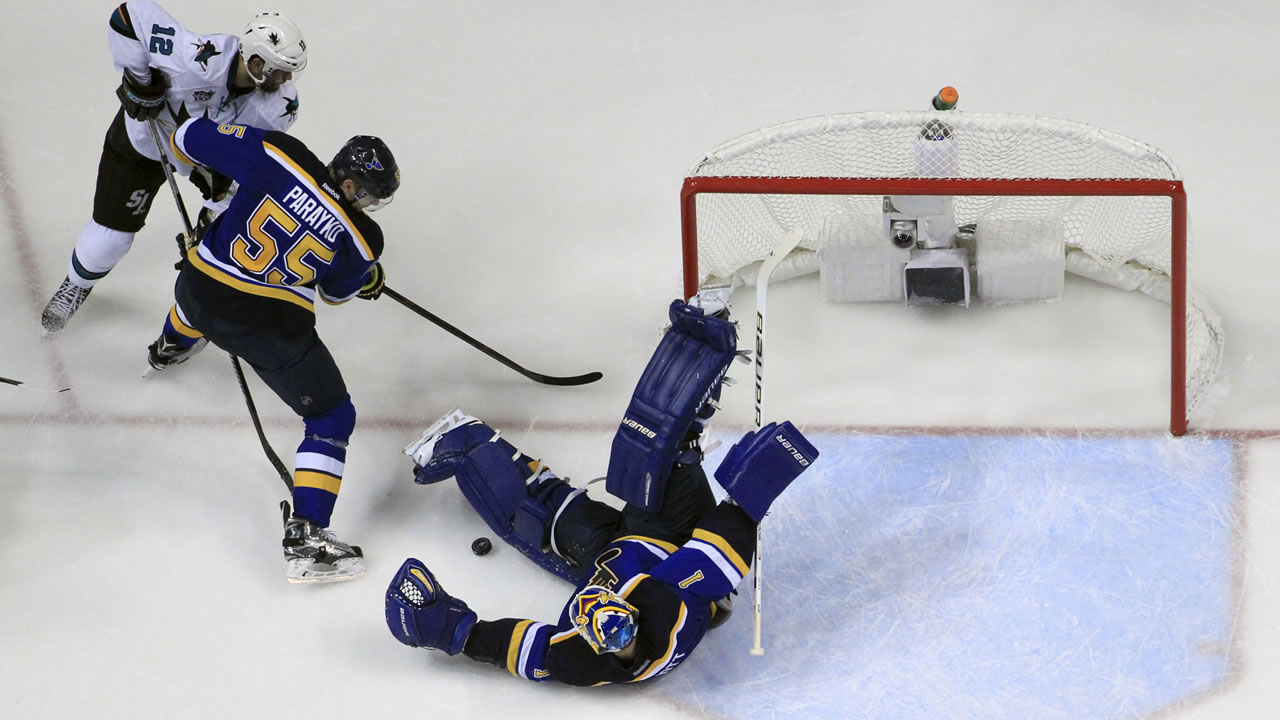 Blues' Elliott makes the save as Sharks' Marleau and Blues' Parayko battle for the puck during Game 1 of the Western Conference Finals on May 15, 2016, in St. Louis. (AP Photo)