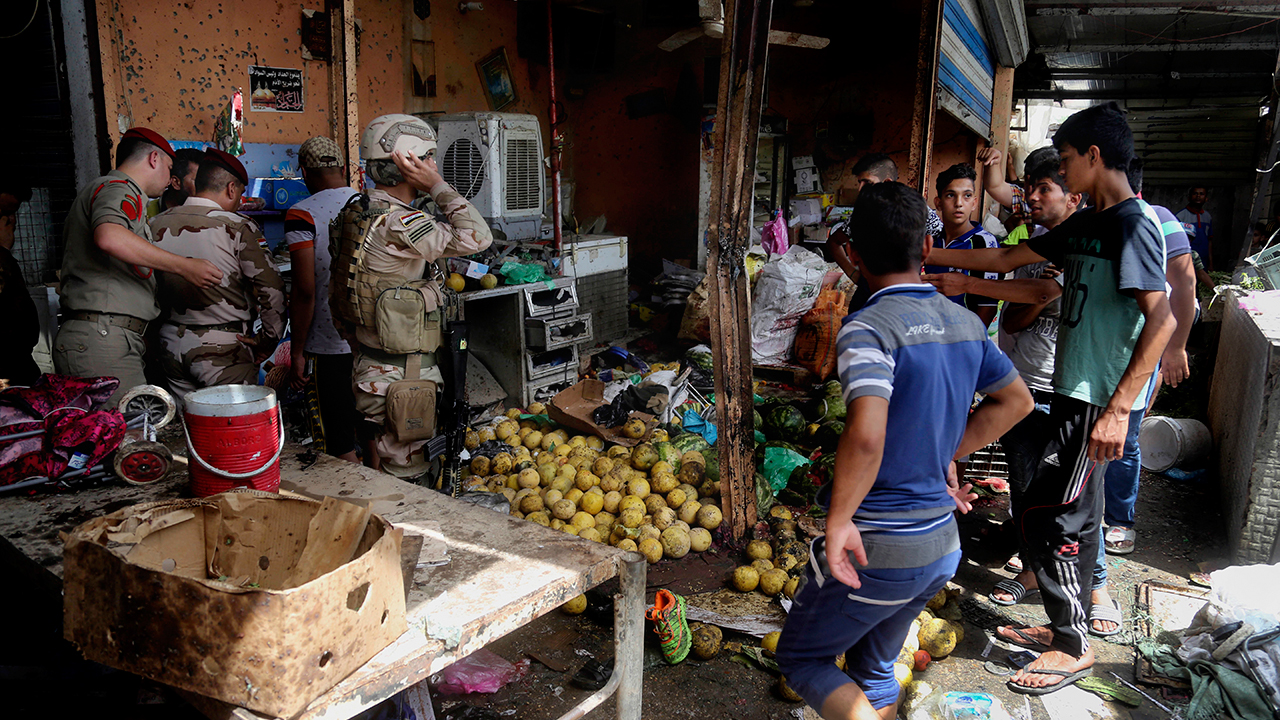 Security forces and citizens inspect the scene after a bomb explosion at an outdoor market in Baghdad's northern neighborhood of Shaab, Iraq, Tuesday, May 17, 2016.