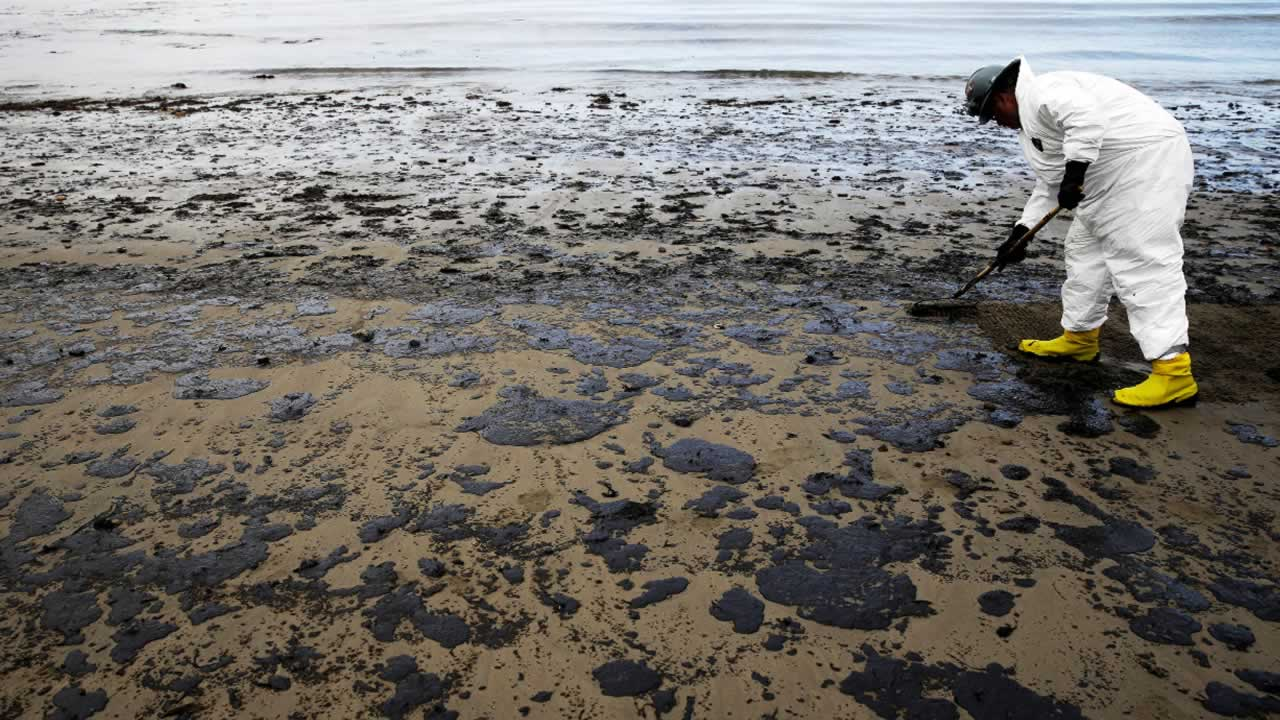 In this May 21, 2015, file photo, a worker removes oil from sand at Refugio State Beach, north of Goleta, Calif.