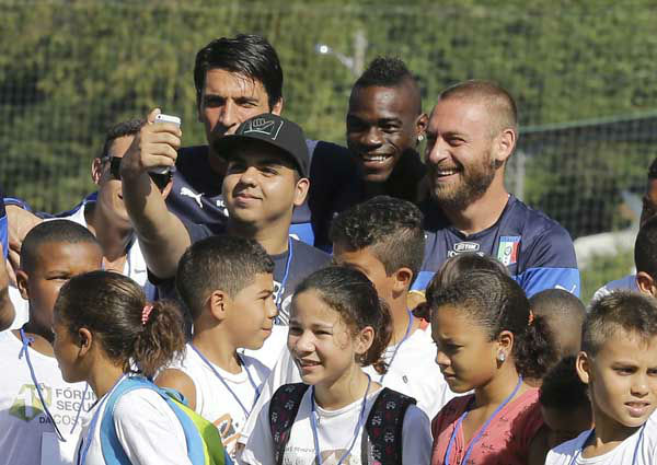 "<div class=""meta image-caption""><div class=""origin-logo origin-image ""><span></span></div><span class=""caption-text"">Italy's players, from left, Gianluigi Buffon, Mario Balotelli, and Daniele De Rossi pose for photos with children prior to training in Mangaratiba, Brazil (Photo/Antonio Calanni)</span></div>"