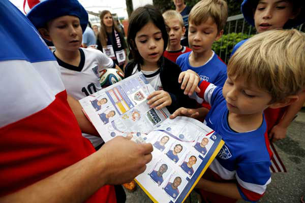 "<div class=""meta image-caption""><div class=""origin-logo origin-image ""><span></span></div><span class=""caption-text"">Flavio Aquino, of San Diego, holds up a sticker book with portraits of the U.S. men's soccer team players as children gather around outside the Sao Paulo FC training center (AP Photo/ Julio Cortez)</span></div>"