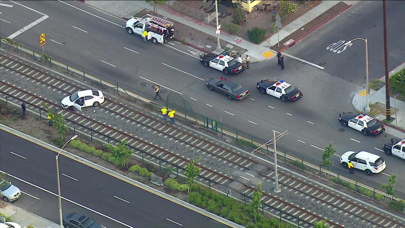 A car is seen stuck on the Metro Expo Line train tracks in Exposition Park on Monday, May 23, 2016.
