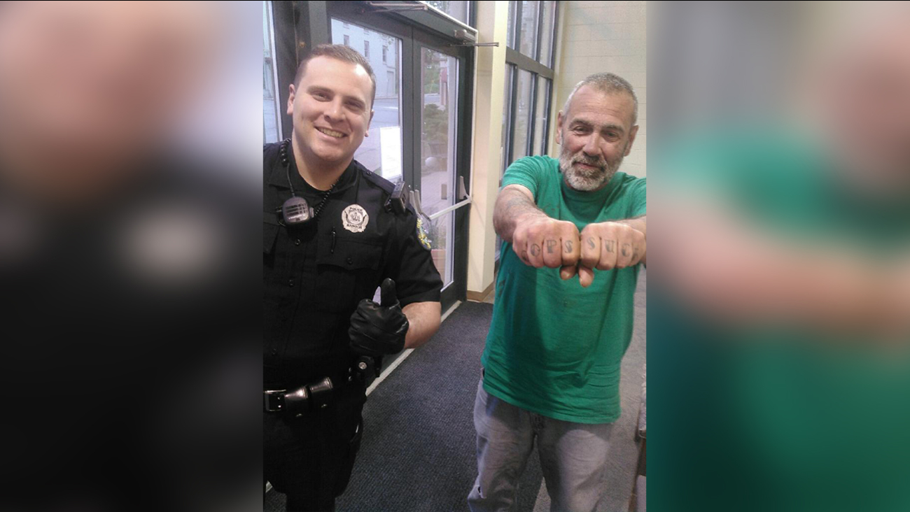 "In a Saturday, May 21, 2016 photo provided by the Bangor PD, officer Keith Larby give a thumbs up next to Russell Johnson, who has ""Cops Suck"" tattooed on his knuckles"