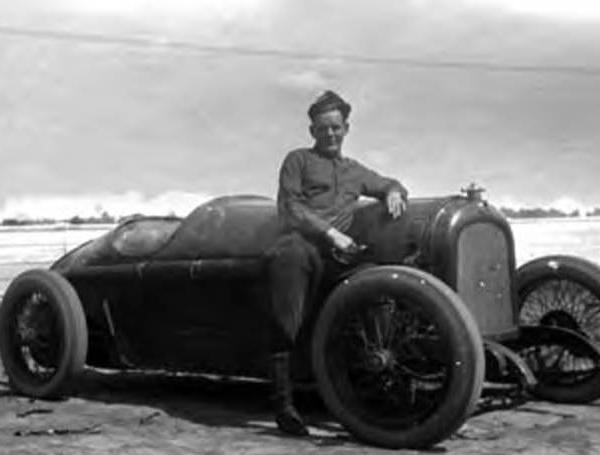 "<div class=""meta image-caption""><div class=""origin-logo origin-image ktrk""><span>KTRK</span></div><span class=""caption-text"">Unidentified man standing beside a race car (Houston Public Library)</span></div>"