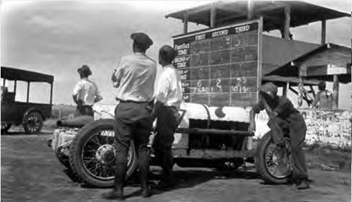 """<div class=""""meta image-caption""""><div class=""""origin-logo origin-image ktrk""""><span>KTRK</span></div><span class=""""caption-text"""">Four men standing beside a racecar. Beyond racecar is a scoreboard with spaces to show the racing time for first second and third racecars. (Houston Public Library)</span></div>"""