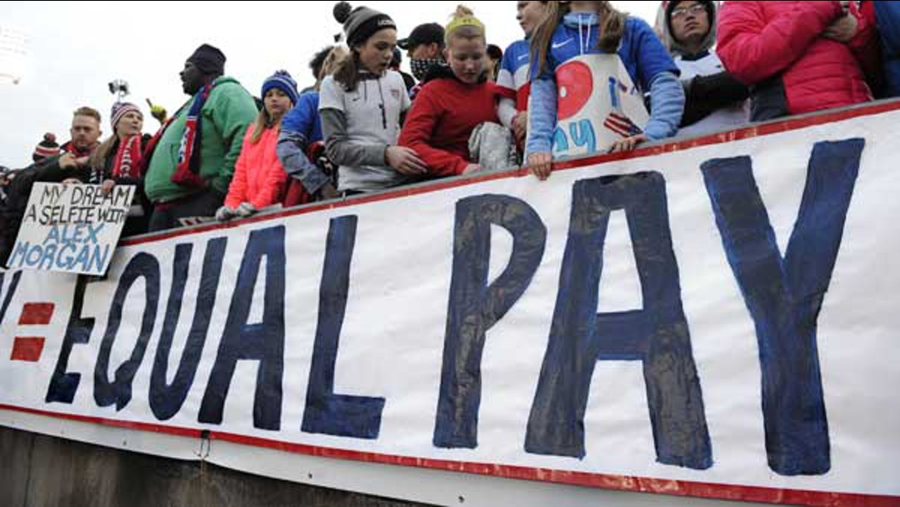Fans stand behind a large sign for equal pay for the women's soccer team during an international friendly soccer match between the United States and Colombia.