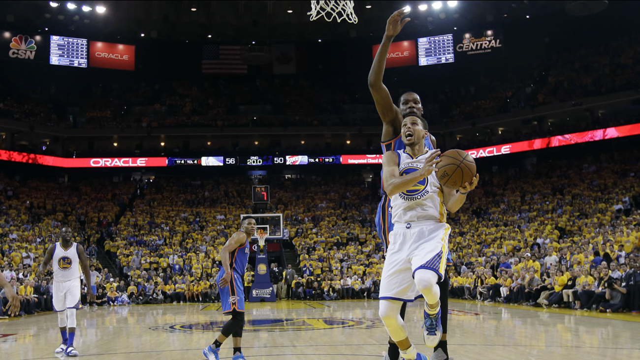 Golden State Warriors' Stephen Curry, right, drives past Oklahoma City Thunder's Kevin Durant, behind Curry, in Game 5 of the NBA basketball Western Conference Finals May 26, 2016.