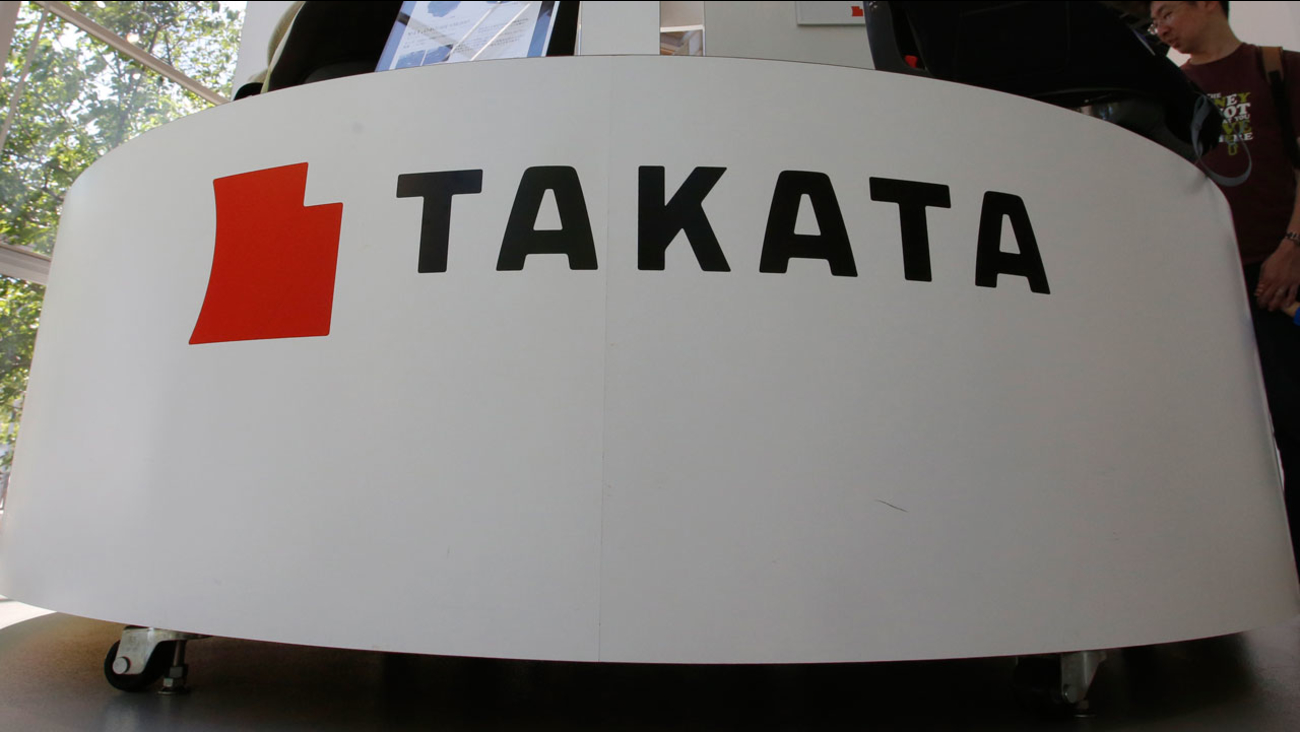 In this Wednesday, May 4, 2016 photo, visitors look at child seats manufactured by Takata Corp. at an automaker's showroom in Tokyo.
