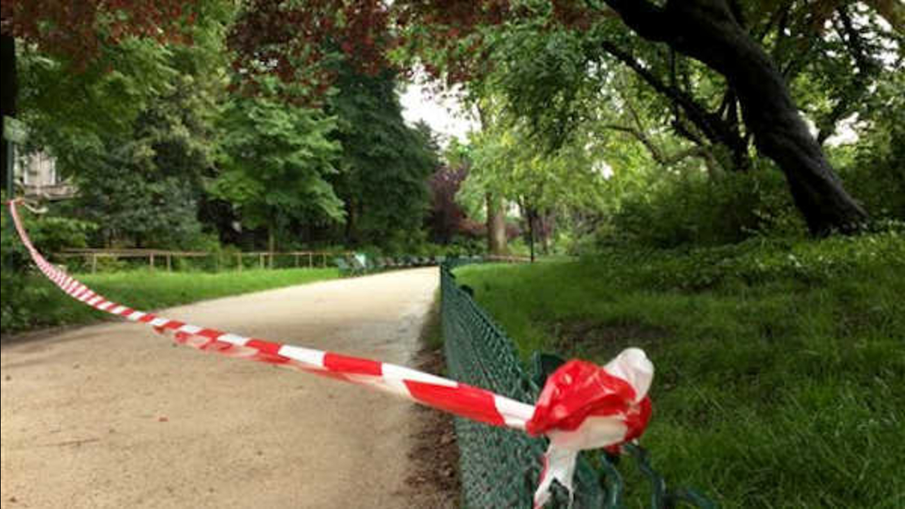 White-and-red tape is strung across a sandy pathway through Park Monceau after a lightning stike, in Paris.