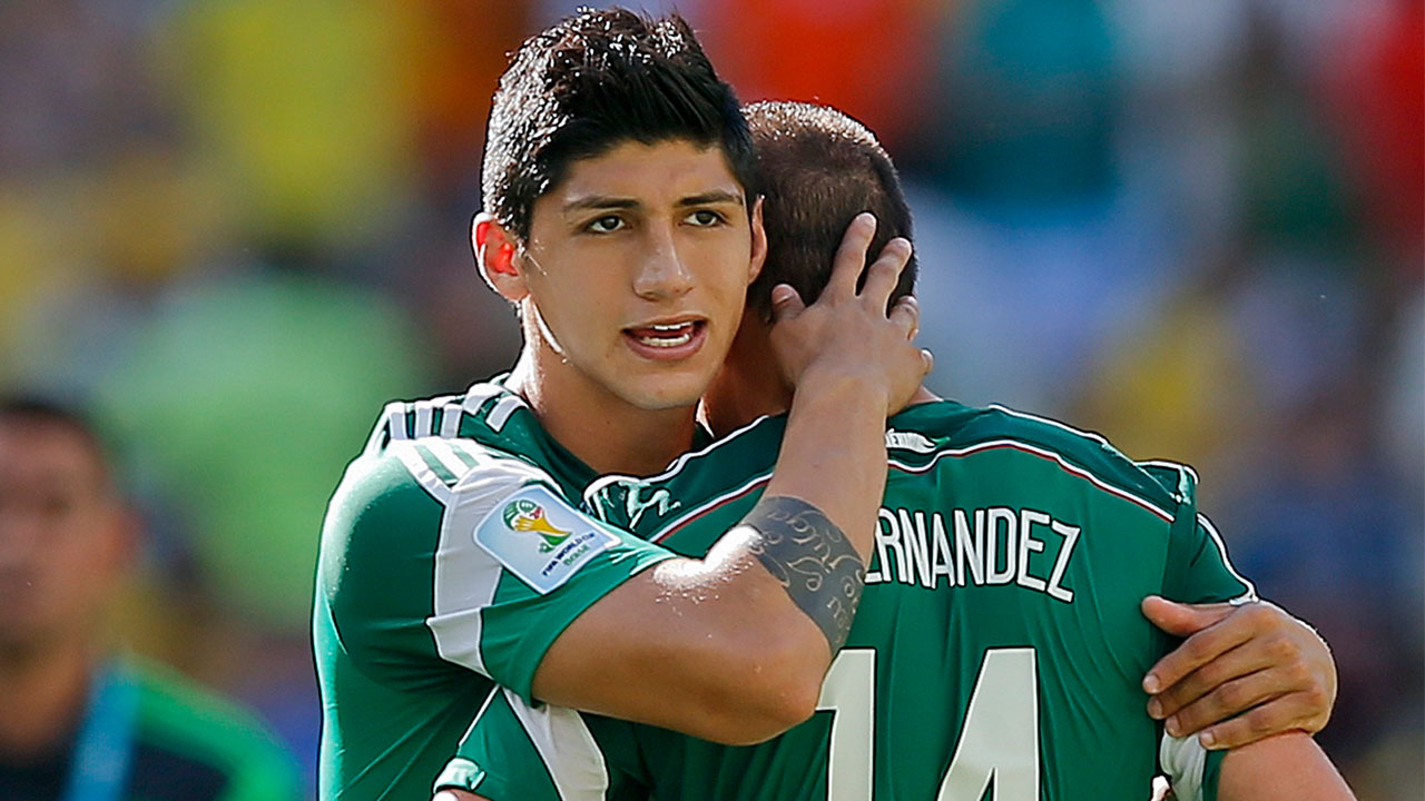 In a June 29, 2014 file photo, Mexico's Alan Pulido consoles teammate Javier Hernandez after the Netherlands defeated Mexico 2-1 during the World Cup.
