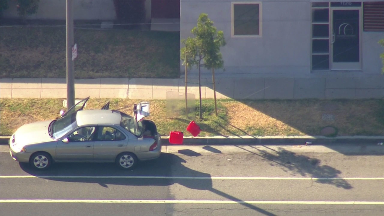 Police use a rope to remove liquid containers from the car belonging to the UCLA gunman which was found in Culver City.