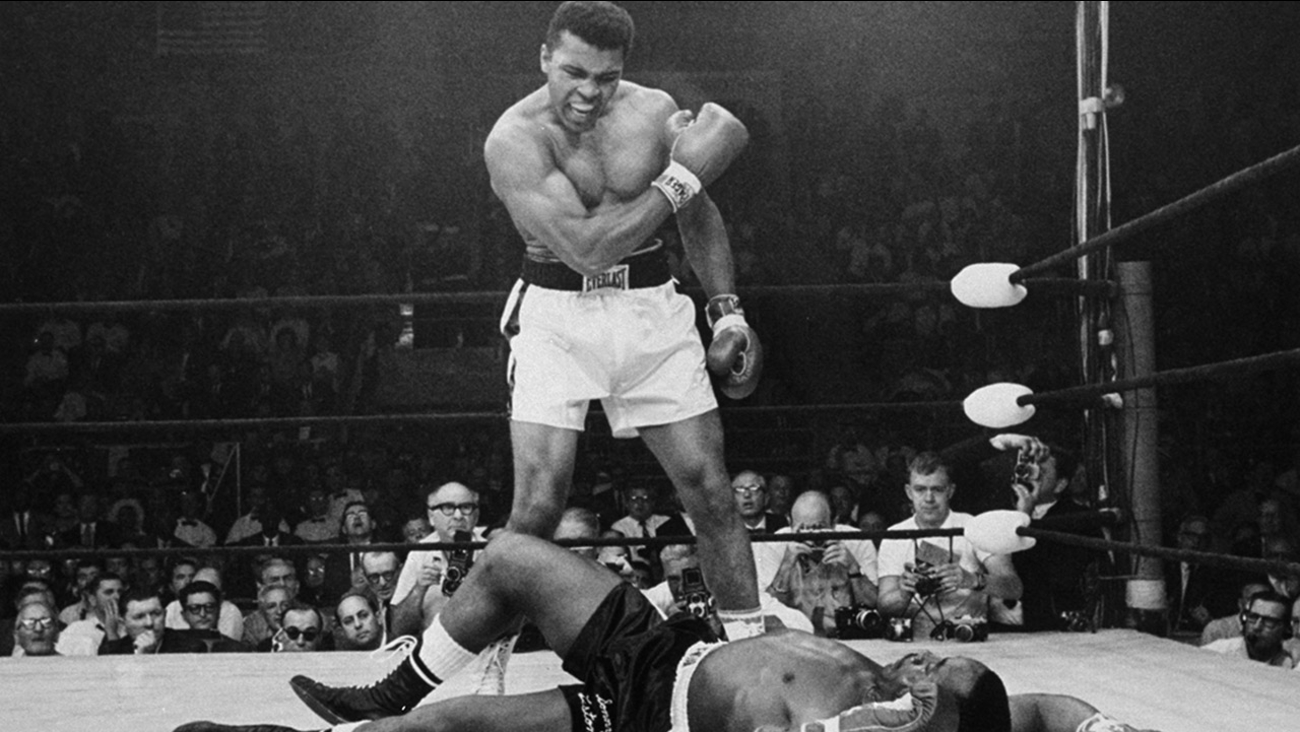 Muhammad Ali stands over fallen challenger Sonny Liston, shouting and gesturing shortly after dropping Liston with a punch on May 25, 1965, in Lewiston, Maine.
