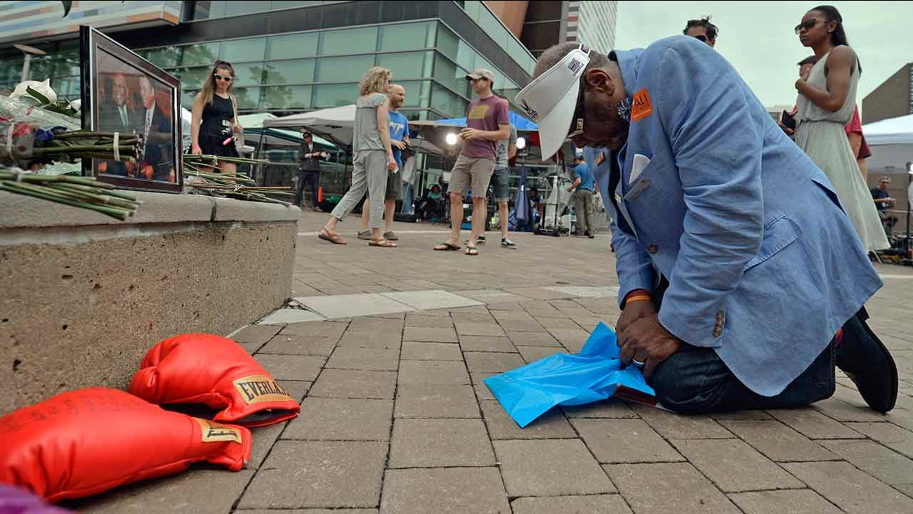 Frank Green, of Louisville, Ky., kneels to pray at a memorial for Muhammad Ali at the Muhammad Ali Center, Saturday, June 4, 2016 in Louisville Ky.