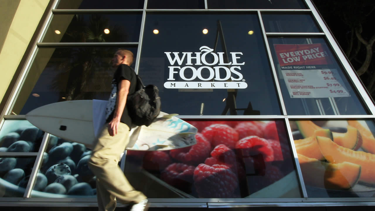 In this Oct. 31, 2011 photo, a man carries a surfboard past a Whole Foods store in Santa Monica, Calif. (AP Photo/Reed Saxon)