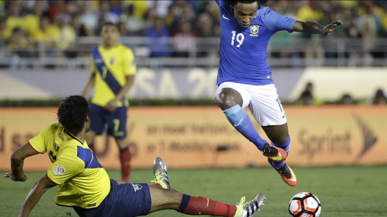 Brazil's Willian, right, avoids a tackle from Ecuador's Arturo Mina during the second half of a Copa America Centenario Group B soccer match at the Rose Bowl, Saturday, June 4, 2016, in Pasadena, Calif.